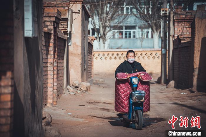 图为宋敏每天骑着电动车给社区居民送生活物资。 刘升 摄