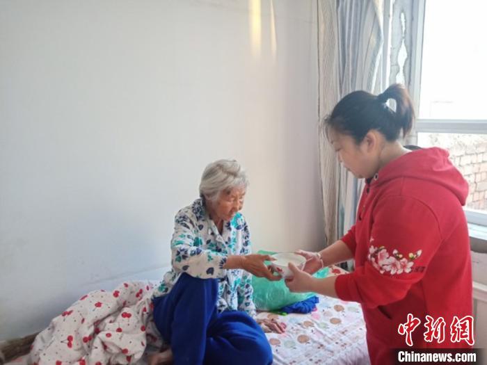 图为宋敏照顾老人吃饭。 宋敏供图 摄