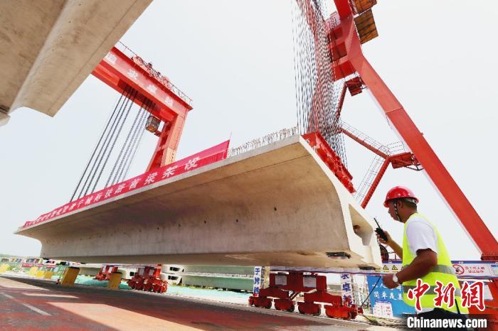 6月30日上午,施工人员正在将重632吨、长34.9米的箱梁缓缓吊起。 韩新亮 摄