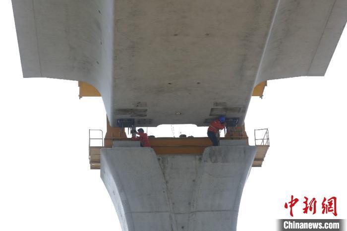 滁宁城际铁路箱梁架设精确至毫米。图为施工人员进行落梁前的最后调整。 韩新亮 摄